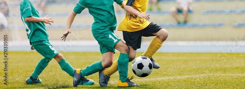 Young Junior Football Match. Players Running and Kicking Football Ball