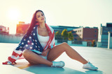 Young woman sitting covered by USA flag outdoors - 210336827