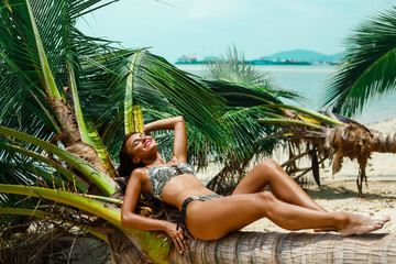 A beautiful tanned girl in a green swimsuit and sunglasses lies on the trunk of a palm tree on a tropical island beach. Summer vacation, travel around the world, advertising swimwear new season