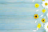 White daisies and garden flowers on a light blue worn wooden table. The flowers are arranged side, empty space left on the other side.
