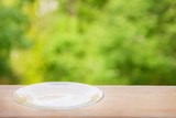 Transparent plate on wooden table against foliage - 210369435