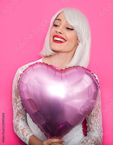 Young smiling woman holding balloon - 210413626