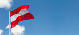 Flag of Austria waving in the wind on flagpole against the sky with clouds on sunny day, banner, close-up