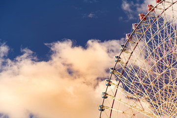 Path of funfair ferris giant wheel with blue sky and white clouds