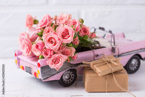 Retro samochód zabawka z róż i zawijane pudełka z kwiatami przedstawia przeciwko białej ścianie teksturowane.
