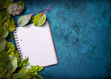 Open recipe book with fresh herbs on grungy blue background - 210433011
