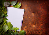 Open menu book with fresh greens on rusty background - 210433086