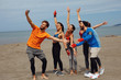 Group of young sports people doing seflie on the beach by the sea
