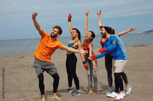 Group of young sports people doing seflie on the beach by the sea - 210436623