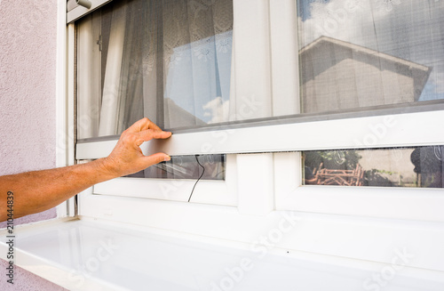 hand holds anti-insect mosquito net on pvc windows - 210444839
