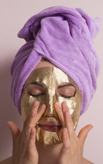 Joven mujer con mascara facial dorada.