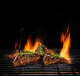 Beef steaks being grilled, isolated on black - 210457044
