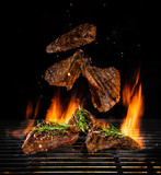 Flying beef steaks on grill with Fire flames - 210457206