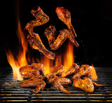 Flying pieces of chicken meat on grill - 210457296