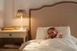Leinwanddruck Bild - Cute little girl with teddybear lying under blanket in her bed and sleeping