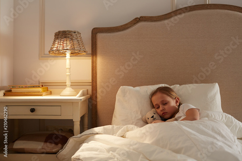 Leinwanddruck Bild Cute little girl with teddybear lying under blanket in her bed and sleeping