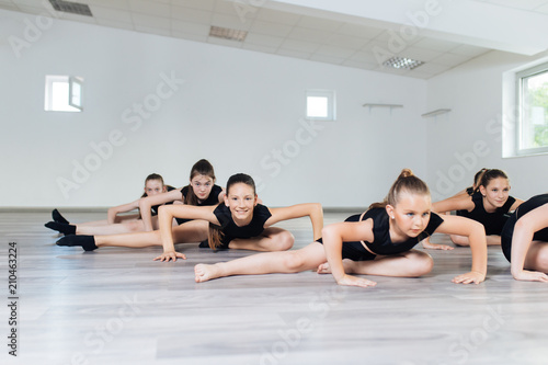 The group of beautiful teenage girls practicing modern ballet dance.