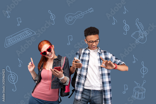 Energetic music. Happy active students feeling good and dancing while wearing earphones and listening to music - 210463423