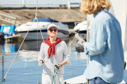 Senior man in sunglasses talking to his assistant while preparing yacht for sailing