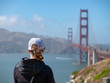 Rearview of woman in baseball cap looking out at Golden Gate Bridge and Marin Headlands