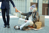 Street person. Poor helpless street person feeling lost while sitting on the street begging for help and some money