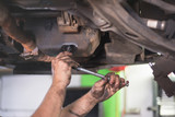 Car mechanic removing used engine oil - 210498625