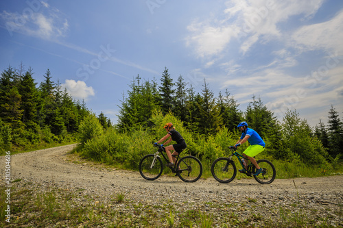 Leinwanddruck Bild Cycling woman and man riding on bikes at sunset mountains forest landscape. Couple cycling MTB enduro flow trail track. Outdoor sport activity.