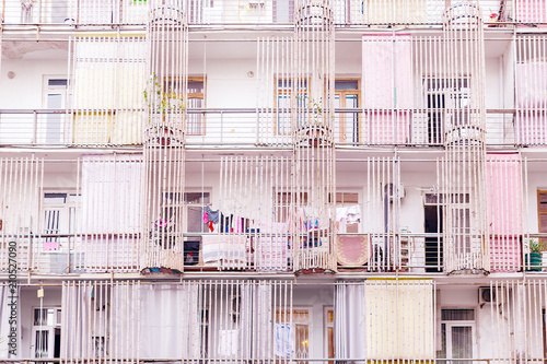 Facade apartment house, decorated with bamboo trunks, drying clothes hanging on a clothesline. Abstract faded background, city everyday life. Toned in pink pastel colors. Batumi, Georgia.. - 210527090