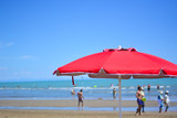 An open red umbrella on the beach - 210535299
