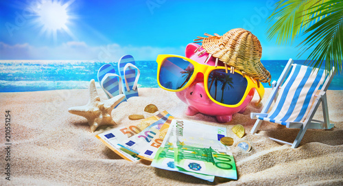 Piggy bank with sunglasses relax on the beach holiday