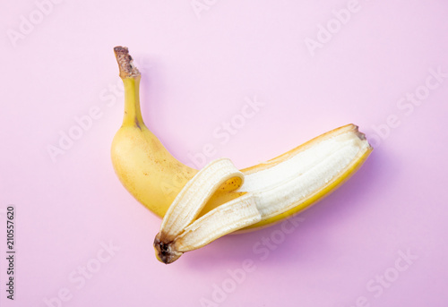 yellow banana on clear pink background. Above view