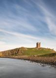 Landscape image of Dunstanburgh Castle on Northumberland coastline in England during late Spring evening - 210580292