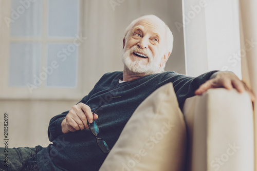Pleasurable time. Joyful senior man smiling while enjoying his rest at home