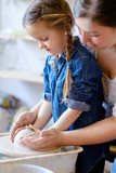 handmade hobby pottery courses. master class at workshop. potter forming clay on turning wheel with a little student girl - 210584674