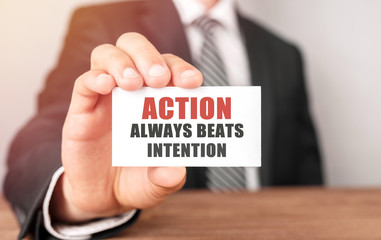 Businessman holding a card with text Action always beats intention