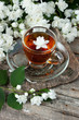 Jasmine flowers  and cup of tea on rustic background