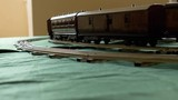 Closeup vintage model electric train formed by a steam locomotive and a green passenger cars running on the rails - 210592872