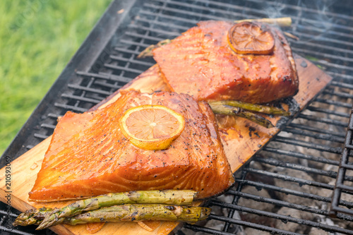 cedar plank salmon with lemon cooking on grill - 210593069