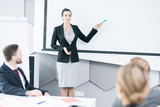 Portrait of young businesswoman giving speech in front of colleagues and pointing at blank projector screen, copy space - 210611275