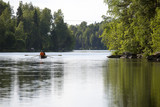 Two people are rowing a boat on a river during summer evening in Finland. - 210620621