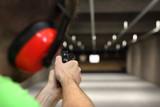 Strzelnica. Strzelanie z pistoletu. Mierzenie do papierowej tarczy na strzelnicy.