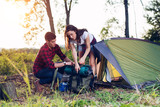Young couple setting up tent outdoors,hiking and camping - 210626247