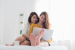 Asian lesbian lgbt couple sitting on bed hug and using laptop computer while drinking hot coffee cup and near white window sunlight in bedroom with happiness moment together,love wins concept.