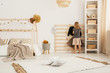 Young girl hanging clothes on wooden hanger in white Nordic style bedroom interior with home-shape bed, two pillows placed on carpet and white rack with wooden boxes