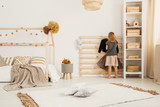 Young girl hanging clothes on wooden hanger in white Nordic style bedroom interior with home-shape bed, two pillows placed on carpet and white rack with wooden boxes - 210635674