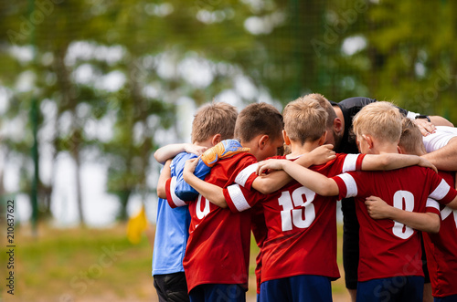 Boys football team with coach. Youth soccer team huddle with coach. Motivation talk, pep talk before the match. Young football soccer players in jersey colorful sportswear