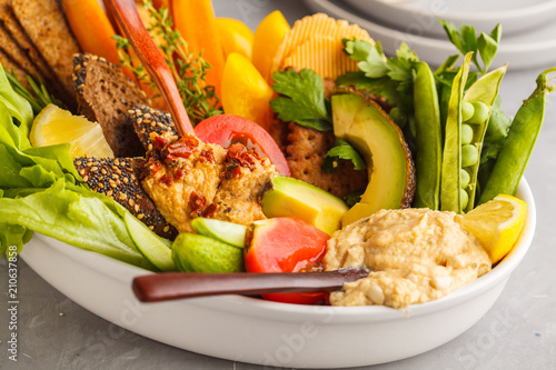 Fototapeta Vegetarian Arabic dip hummus with vegetables and different snacks on a light background. Healthy vegan food concept.