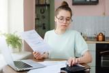 Yong woman budgeting, managing utilities expences, writing financial plan, analyzing her spendings - 210638480