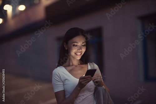 Fototapeta A young beautiful asian woman using an application in her smart phone to read email, send text message, chat, browse or shop online. Communicate about people, phone, technology, applications