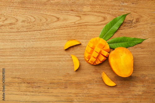 Mango cubes slice with leaf on wooden background - 210639038